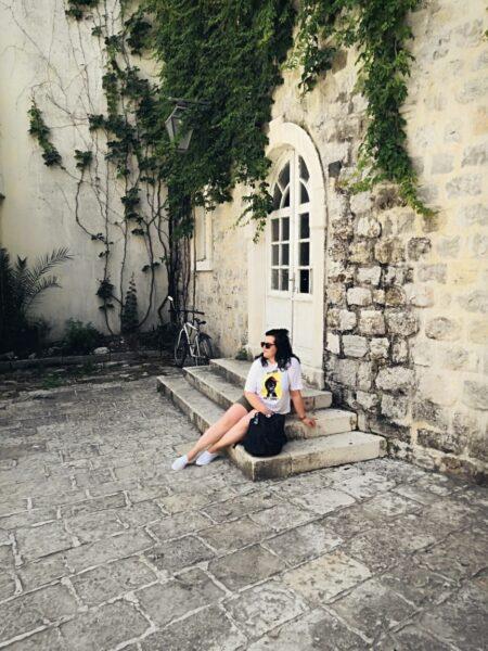 Жена в старом городе на ступеньках